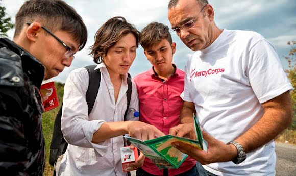 A Mercy Corps field worker consults a map while communicating with refugees.