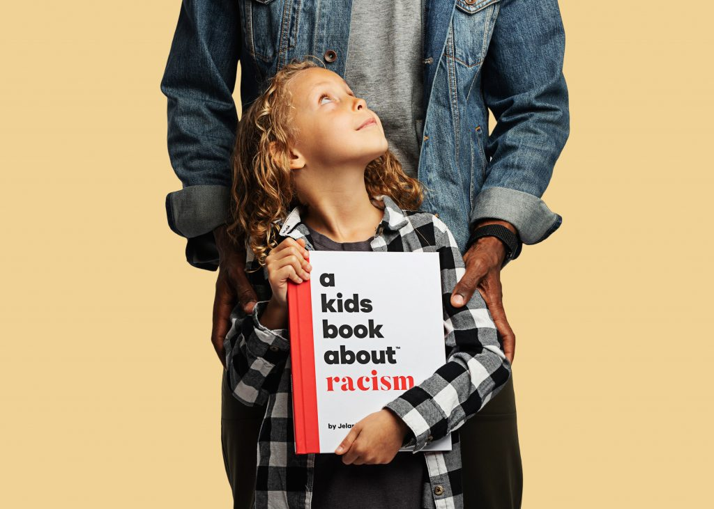 A child holding the book A Kids Book About Racism by Jelani Memory, while adult embraces the child