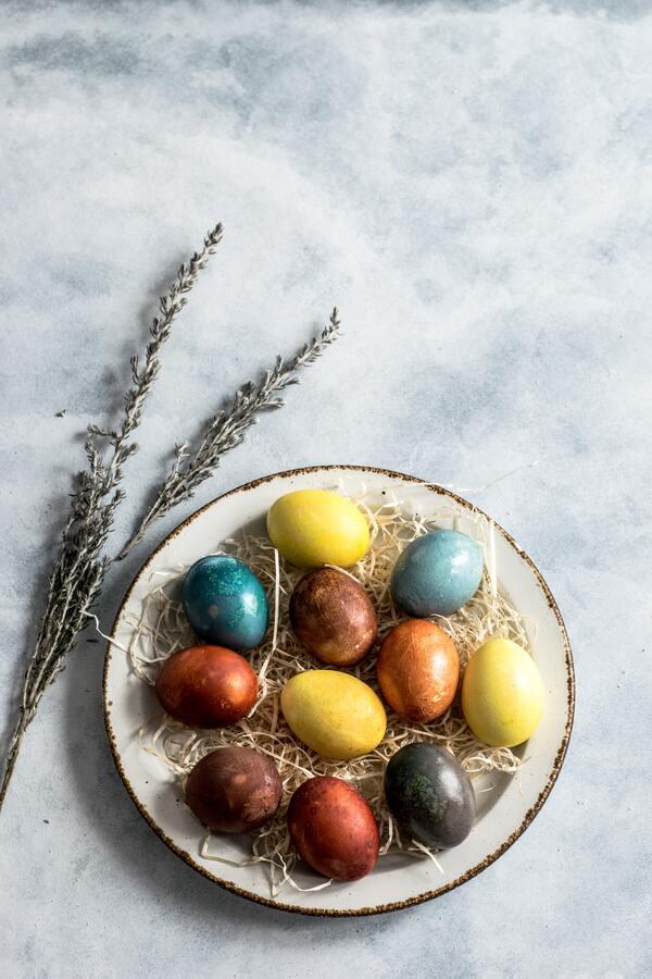 Um prato com ovos coloridos no tema de páscoa ao lado de uma planta seca