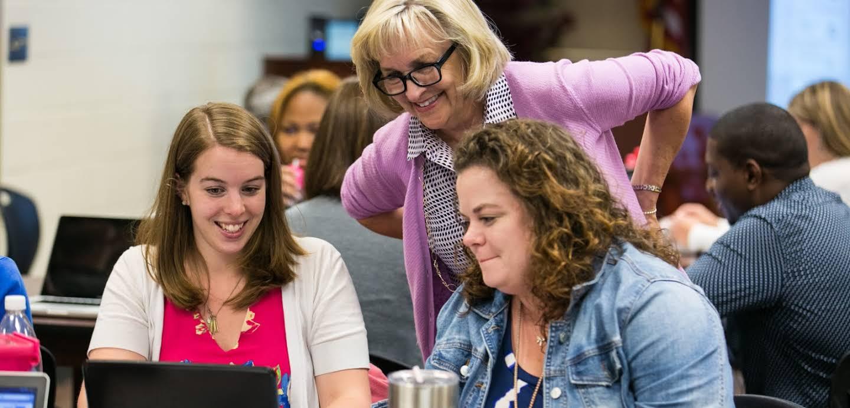 Três mulheres estão olhando para a tela de um laptop em uma conferência.