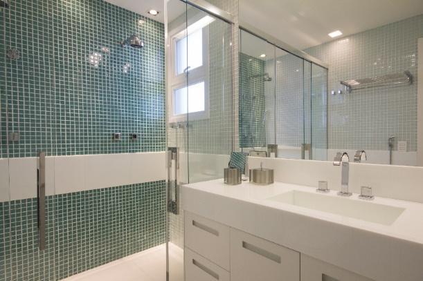 Banheiro com box de vidro, área dentro do box revestida de pastilhas verdes, gabinete e pia branca.