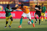 Ivory Coast's Jonathan Kodjia shrugs off South Africa's Buhle Mkhwanazi before firing home the only goal of the match during an Afcon Groud D encounter in Cairo on June 24 2019.
