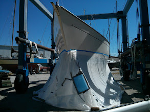 Photo: We used lighter weight and less expensive 4 mil plastic sheeting for the sides of the tent. The upper edge is tapped to the hull above the water line. The lower edge is rolled inward together with the base and then weighted down with scrap lumber.