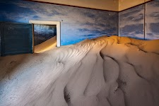 door wind opgestuwd zand in een ruimte met blauwe wanden
