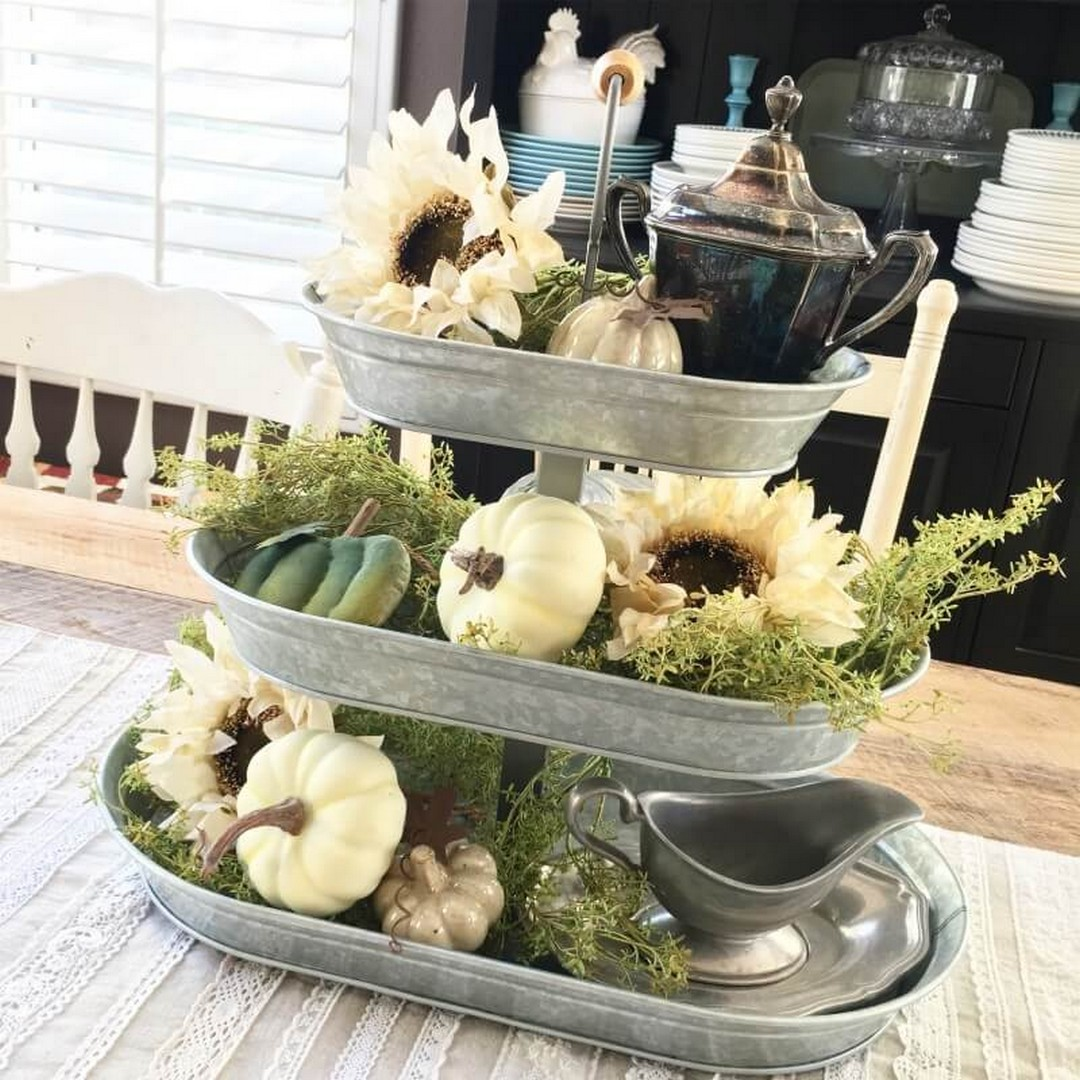 metal three tiered tray with mini pumpkins, flowers and vintage dishware