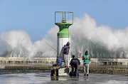 A wave crashes into the harbour wall in Kalk Bay, near Cape Town.