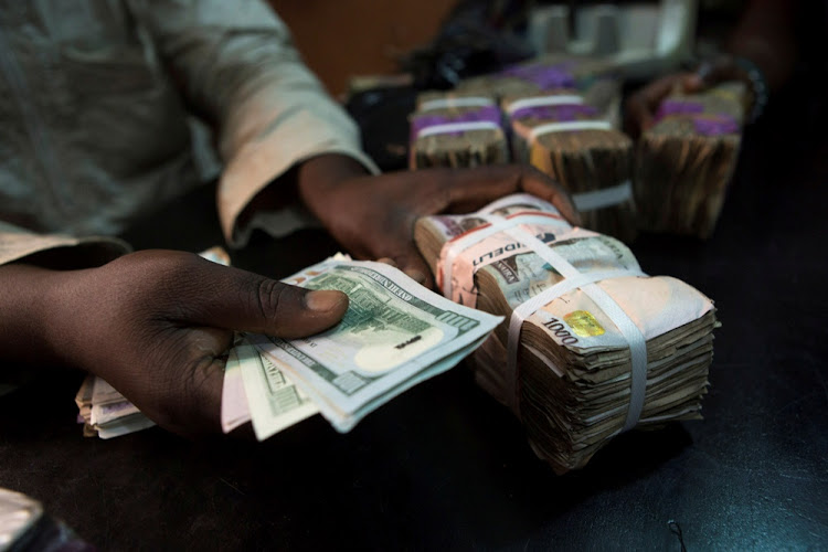 A trader changes dollars with naira at a currency exchange shop in Lagos, Nigeria. Picture: REUTERS/Joe Penney
