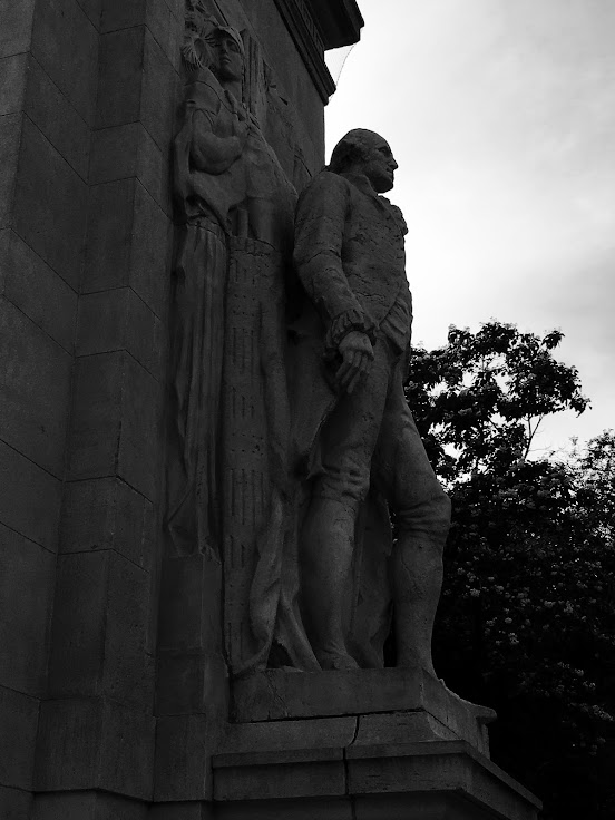 A statue of George Washington stands before the arch.