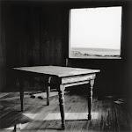 lege, houten tafel op planken vloer in licht van open raam
