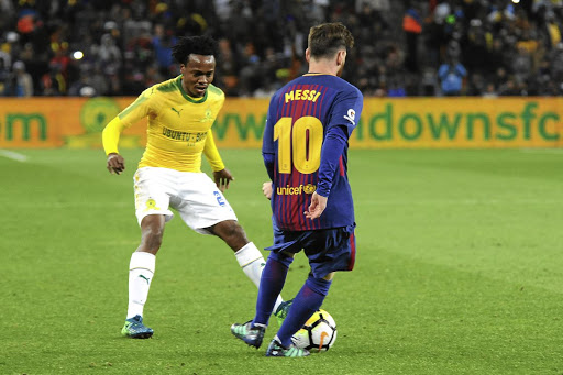 Sundowns star Percy Tau keeps a close eye on Barcelona's Lionel Messi during their friendly match at FNB Stadium last night.