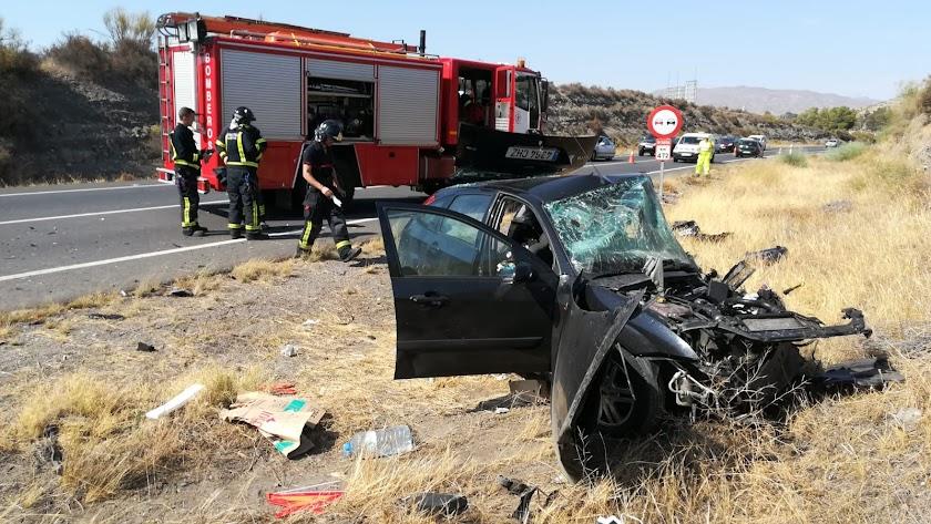 Los Bomberos de Almería junto a uno de los vehículos siniestrados.