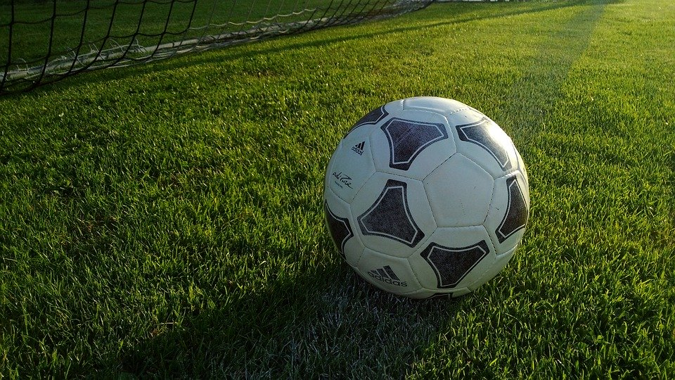 A football sits on a football pitch with a football goal just behind it