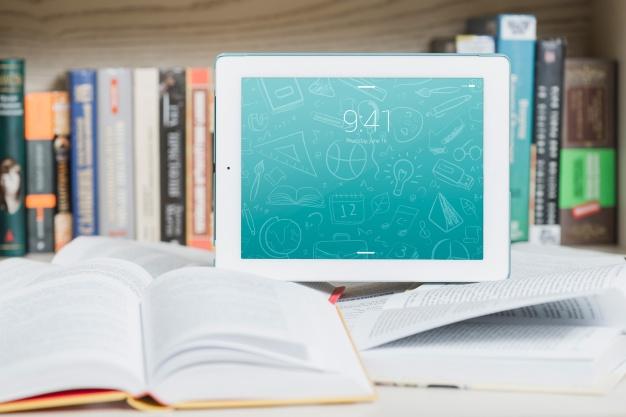 Foto de um tablet posicionado sobre livros, em cima de uma mesa, com o fundo de uma estante de livros. Essa imagem visa exaltar a importância da gamificação na educação.