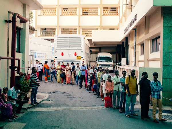 Patients stand in a line outside of Sankara Nethralaya Eye Hospital