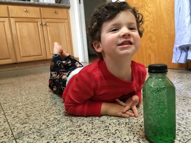 Smiling toddler boy lying in front of glitter bottle