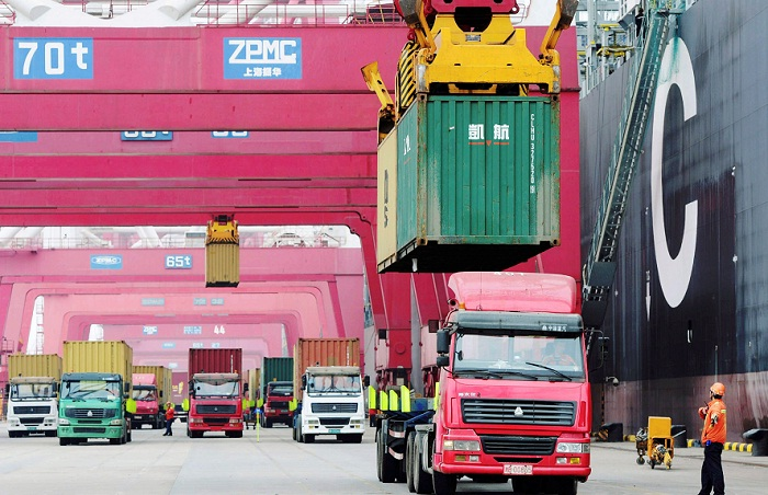 Trucks are loaded with shipping containers at a port in Qingdao in China's Shandong province. Picture: REUTERS
