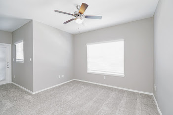 Living room with plush carpet, light gray walls, and ceiling fan
