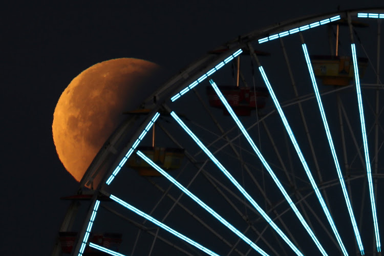 A lunar eclipse of a full 'blue moon'hovers above the big wheel on the Santa Monica Pier in California on Wednesday.