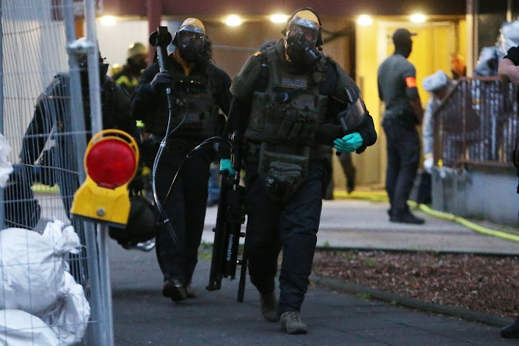 "Police officers, including special forces wearing protective suits walk out of a building in Cologne, where German police have arrested a Tunisian man after discovering ""toxic substances"" at his flat on June 12 2018."