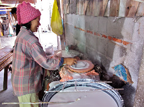 Photo: spreading a thin layer of rice batter onto cloth covering a steamer pot