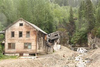 """Photo: """"The Kennecott hospital (left) stood out as the town's only white-washed building. The vast majority of other town structures, including workers' bunkhouses (right), were painted red, the least expensive color at the time. The Kennecott hospital was also the site of the first x-ray machine in Alaska."""""""