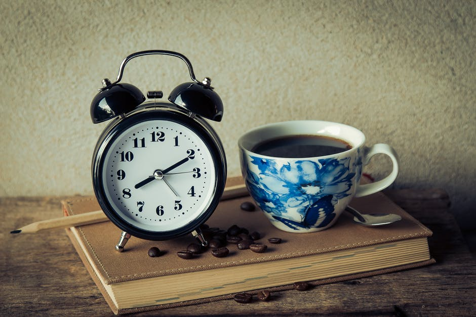 alarm clock, black coffee, book