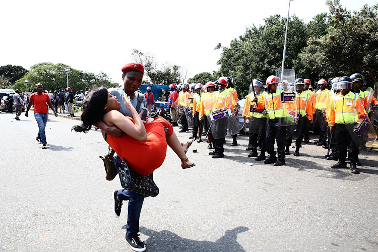 University of KwaZulu-Natal's Howard College student Nathi Phetha carries fellow student Bongeka Mntaka, who was allegedly shot with a rubber bullet by police. Picture: SOWETAN.