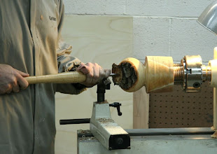 Photo: Beginning hollowing with a gouge. Note the large volume of wood left on the headstock for stability and strength. Keith then goes under the shoulder with a small Sorby bent tool.