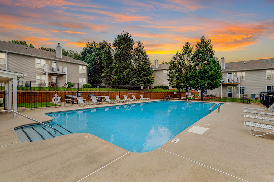 Brentwood community pool with reclining lounge chairs at dusk