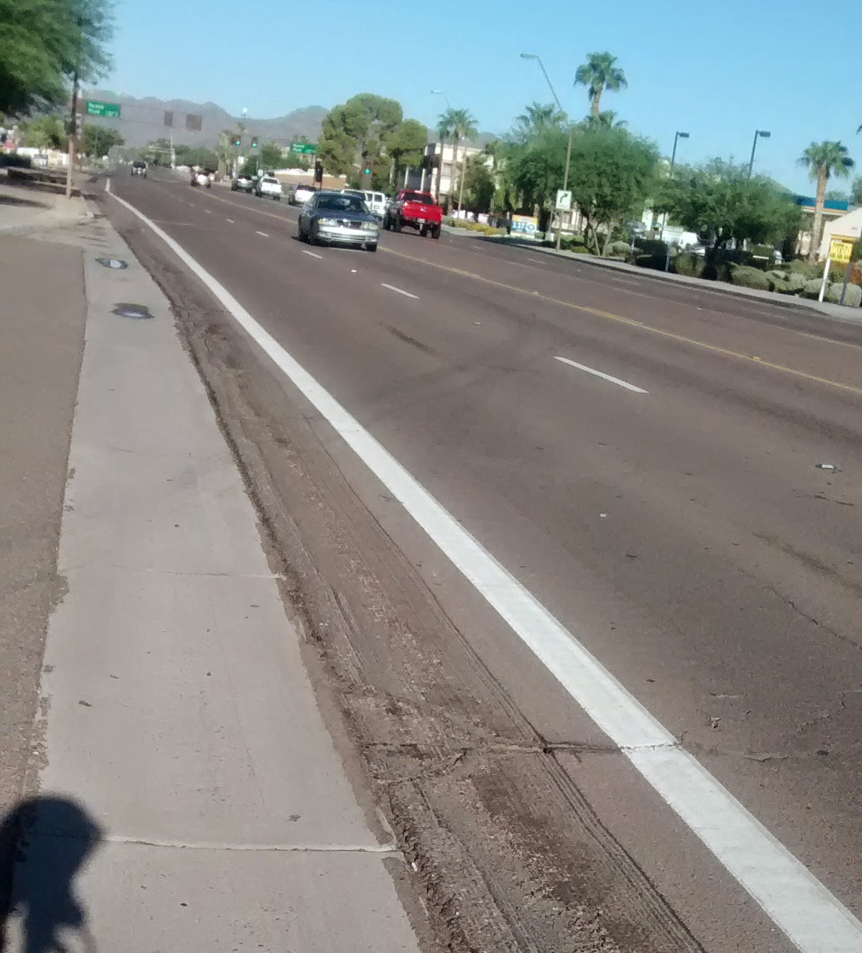 """Photo: Warner Rd, eastbound; about 200' east of intersection with Kyrene. City of Tempe tried to fix the high asphalt by grinding (sometime in early August 2014). This remains dangerous, as it is first of all too narrow; and second the asphalt has already crumbled next to the concrete leaving a very irregular surface. Bike lanes are supposed to have a minimum of 4' of CONSISTENT surface width. It's only about 2' wide at the """"pinch point"""" (in the pic it's near the puddle in the gutter).  Note that at the same time, the city (correctly in my view), fixed a similar large height-irregularity in the asphalt closer to the intersection by digging out and resurfacing a strip of asphalt next to the flat concrete gutter. #edgehazard"""