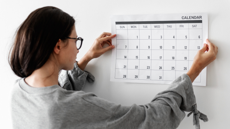 A woman setting up a calendar on her wall