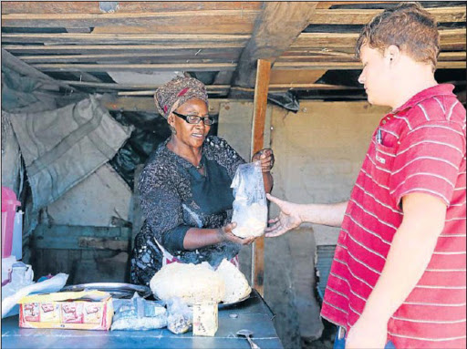 Zoliswa Simandla, an informal business owner in Fort Jackson, helps her customer Jaundre Olivier. Picture: SIBONGILE NGALWA