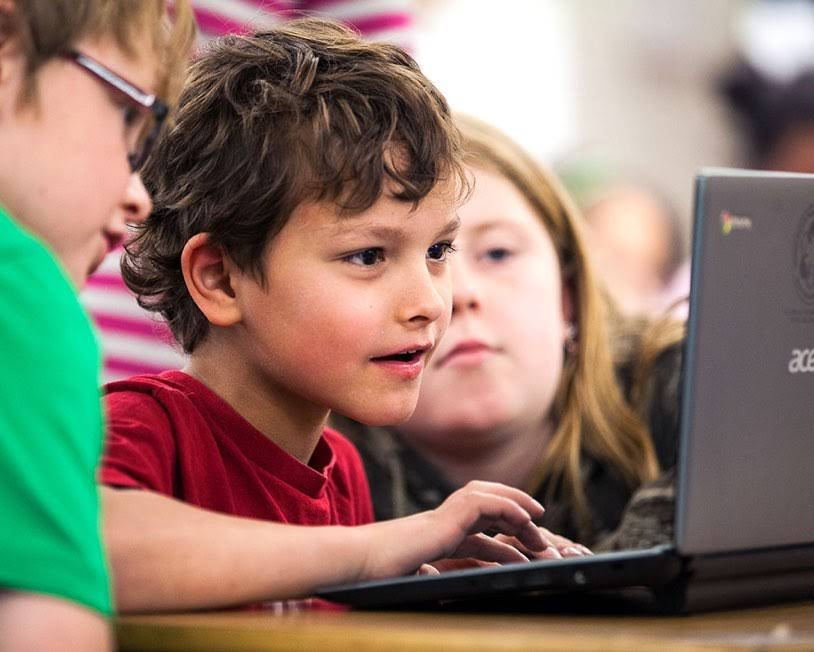 A young boy stares intently at his Chromebook while fellow students look over his shoulder.