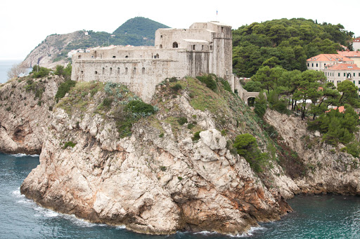 A close-up of the fortress atop a promenade guarding Dubrovnik.