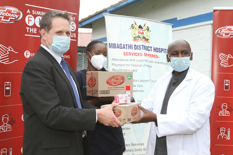 Unilever East Africa MD Justin Apsey presents part of the company's donations of personal hygiene products to In charge of Isolation wards at Mbagathi County Hospital Dr Michelle Musoga and the Deputy Medical Superintendent at the hospital Dr Keizah Nathan
