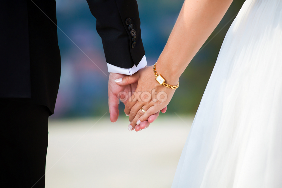 Young married couple holding hands by Cornel Achirei - Wedding Details ( person, lovers, holding, valentine, husband, people, romance, together, caucasian, hand, love, woman, happy, affectionate, couple, men, dating, bride, passion, marry, ring, girlfriend, male, togetherness, romantic, white, happiness, finger, adult, ceremony, marriage, young, human, relationship, two, boyfriend, female, unity, dress, touching, wedding, wife, background, outdoors, matrimony, groom, engagement )
