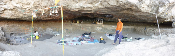 Photo: Panorama of the cave we stayed in under the Chanderi massif. There was a temple to the god Shiva, complete with a lingam, bells, flags, ceramic floor tiles, graffitti, garbage, firewood, clothesline, and a mouse that ran over and kept us awake all night! Rahul Lama on the right prepares our next meal while Richard Kher walks between our gear and sleeping areas.