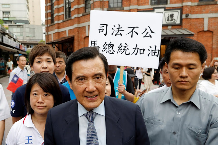 "Members of the Kuomintang hold a placard reading, ""Injustice, President Ma Cheer Up"", as former Taiwanese President Ma Ying-jeou leaves from an event in Taipei, Taiwan on May 15 2018. Picture: REUTERS/ TYRONE SIU"
