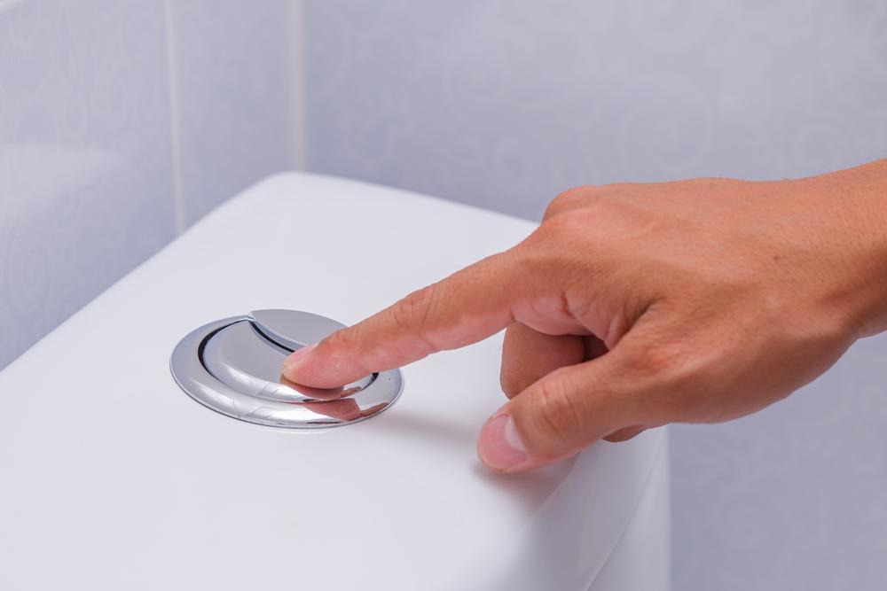 Uma mão apertando uma descarga de banheiro.