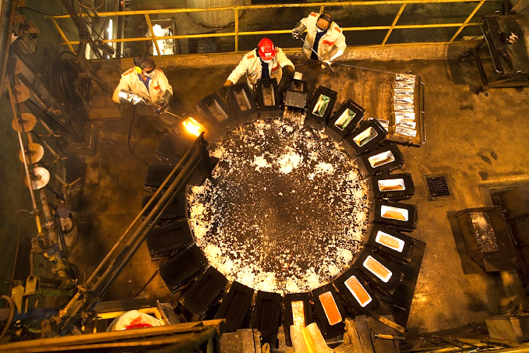 Workers remove bullion bars from moulds at the KHGM Polska Miedz smelting plant in Poland. Picture: BLOOMBERG/BARTEK SADOWSKI