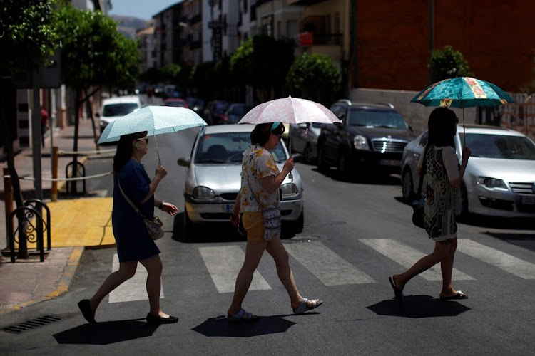 Tourists use umbrellas to take cover from the sun as they walk in a street during a heatwave in Ronda, Spain, June 21, 2017.