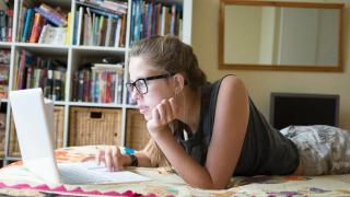 una niña tumbada mirando un portátil