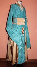 """Photo: Vestido """"Cersei"""" transpassado na frente, em crepe patu azul royal e cetim toque de seda dourado com mangas longas boca de sino e cinto em tela e cetim. A partir de R$300,00. ( Cada figurino é exclusivo e não repetido)"""