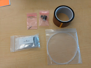"""Photo: The parts bag. Big roll of Kapton tape, feed tube, spare sleeves for the hot-end, bag of spare hardware, and the mysterious """"Glider print HW"""" bag. Turns out, there is a many-hour pre-sliced glider model (http://www.thingiverse.com/thing:22268 ) on the SD card that ships in the RAMBO board, and those are the nose weight."""