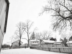 Photo: Black and whit photo of farm houses under snow at Carriage Hill Metropark in Dayton, Ohio.