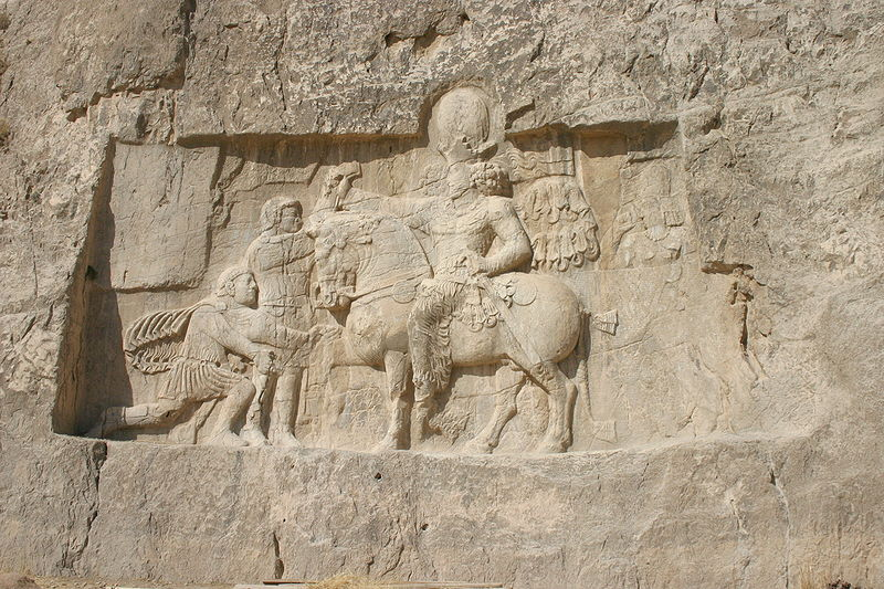 Large wall carving in rock depicting the defeat of the Roman emperor before the Persian king Shapur I on horseback.