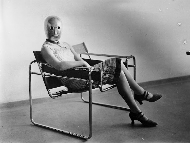 Woman wearing a theatrical mask by Oskar Schlemmer and seated on Marcel Breuer's tubular-steel chair.