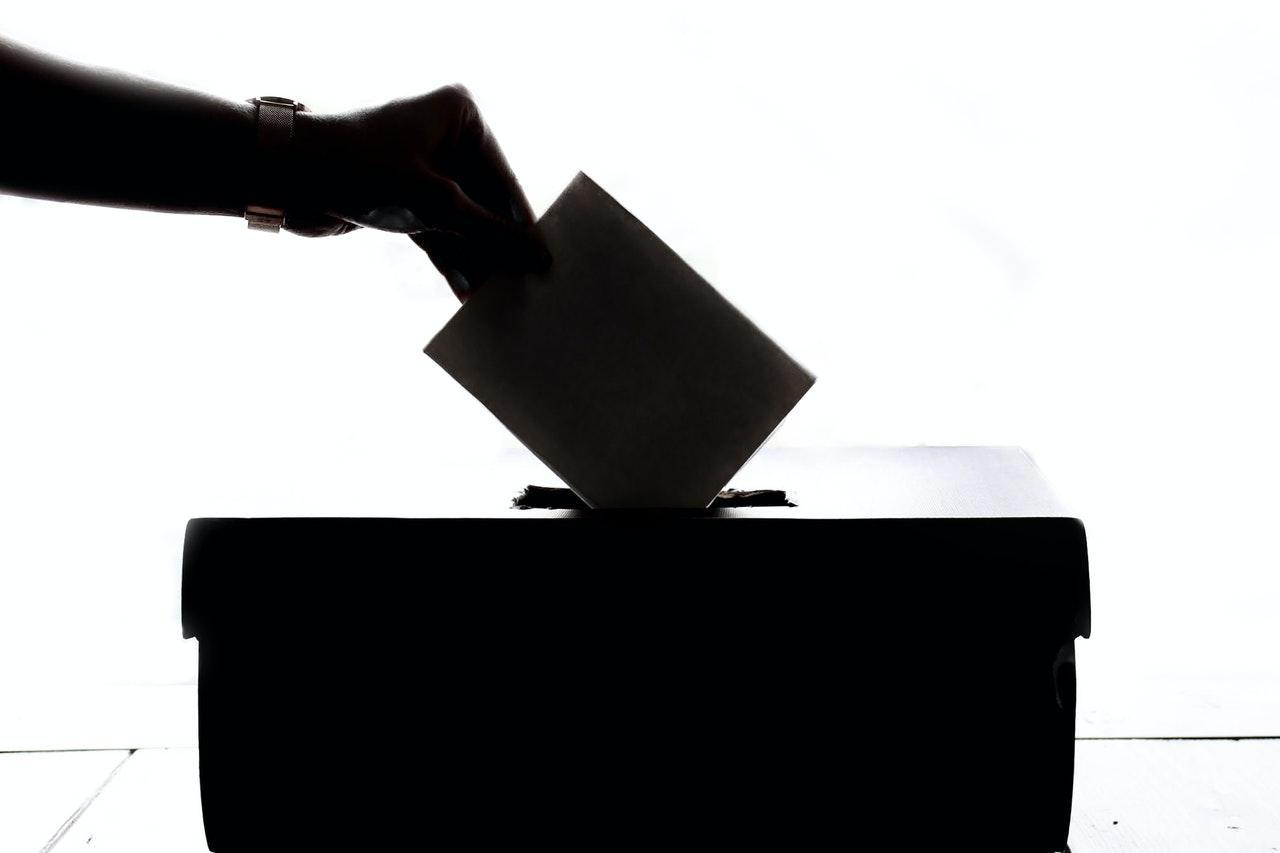 A black and white polling box with a hand putting in a vote