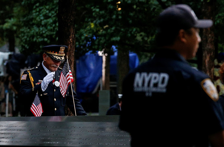 A guest pauses among names at the edge of the south reflecting pool at the 9/11 memorial in New York during ceremonies marking the 17th anniversary of the September 11 2001 attacks on the World Trade Center.