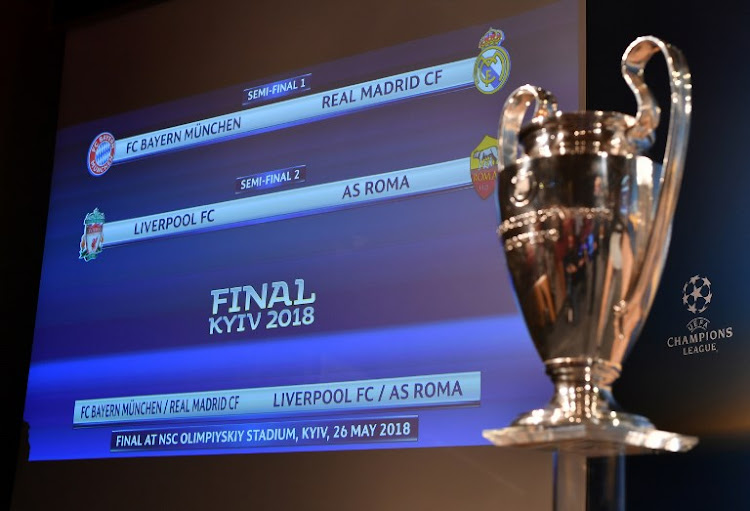 This photograph taken on April 13, 2018, shows a screen displaying the fixtures alongside the trophy after the draw for the semi-finals round of the UEFA Champions League football tournament at the UEFA headquarters in Nyon.